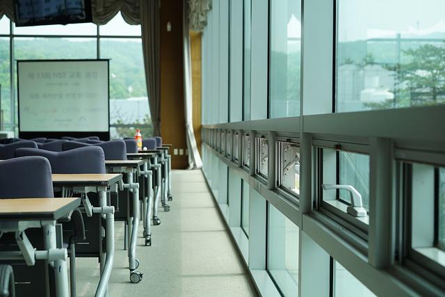 sala z dużym oknem i krzesłami