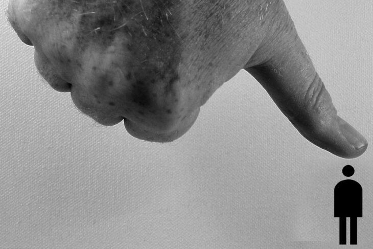 wielki kciuk przygniatający małego czowieka