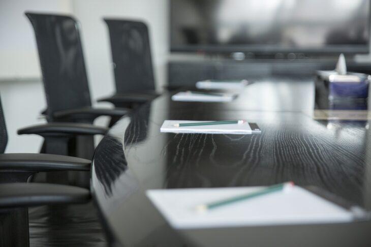 stół konferencyjny na którym leżą notatki i długopisy