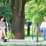 dwie osoby na siedzą na ławce i rozmawiają