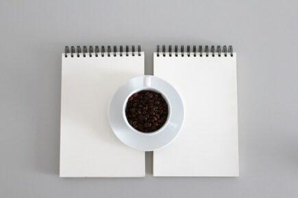 filiżanka z kawą postawiona na białym, czystym notesie
