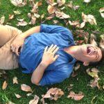śmiejący się facet lezy na trawie